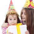 Two little girls with hats holding gift box — Stock Photo