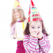 Little girl with birthday hat and her sister with gift in backgr — Stock Photo