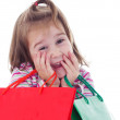 Little girl in shopping with shopping cart and coloured bags — Stock Photo #19285971