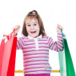 Little girl in shopping with shopping cart and coloured bags — Stock Photo #19285993