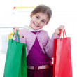 Little girl in shopping with shopping cart and coloured bags — Stock Photo #19286015