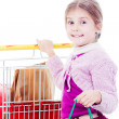 Little girl in shopping with shopping cart and coloured bags — Stock Photo