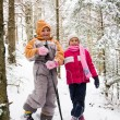 Two little girls in snowy forest - Stock Photo