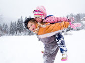Two little girls playing on snow — Stockfoto