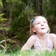 Little girl laying down in the forest — Stock Photo