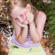 Little girl sitting on tree — Stock Photo