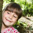Little cute girl  leaning against a tree in the forest — Stock Photo
