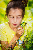 Pretty little girl with magnifying glass looking at flower — Stock Photo