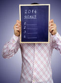 Businessman hiding behind the new year 2014. Board with goals i — Stock Photo