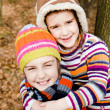 Two little sister girls hug playing in the forest — Stock Photo #40039687