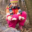 Stock Photo: Little girl lighting fire in forest - dangerous playing