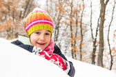 Little girl laying on the snow — Stock Photo