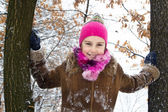 Happy little girl spending a nice time in winter forest — Stock Photo