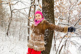 Happy little girl spending a nice time in winter forest — Стоковое фото