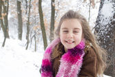Pretty little girl with snow in her long hair — Stock Photo