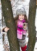 Niña feliz pasar un rato agradable en bosque de invierno — Foto de Stock