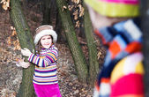 Two little sister girls hug playing in the forest — Stock Photo