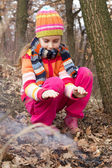 Little girl lighting fire in forest - dangerous playing — Stock Photo