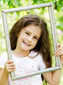 Little girl looking throgh wooden frame - beautiful nature backg — Stock Photo