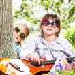 Two little girls have a fun and playing a guitar outdoor — Stock Photo #45780589