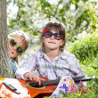 Two little girls have a fun and playing a guitar outdoor — Stock Photo #45780627
