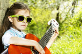Happy little girl with glasses playing guitar outdoor — Stock Photo