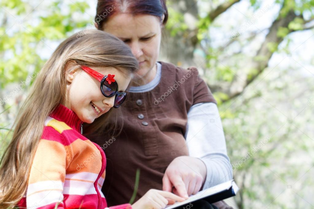 与可爱的小女孩读书的幸福母亲