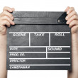 Two male hands holding movie production clapper board isolated o — Stock Photo