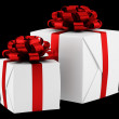 Gift boxes with red ribbons isolated on black background — Stock Photo
