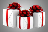 Gift boxes with red ribbons isolated on gray background — Stock Photo