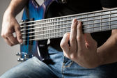Male musician playing on six-string bass guitar — Stock Photo