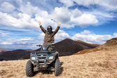 Male rider on ATV at mountain top — Stock Photo