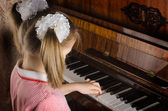 The young girl learns to play a piano — Stock Photo