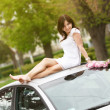 Girl sitting on a car roof — Stock Photo