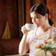 图库照片: Elegant woman with a tea mug in cafe