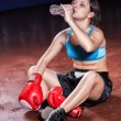 Stock Photo: Girl boxer sitting on floor in hall after tiresome train