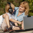 The little boy and mother with the laptop in park — Stock Photo