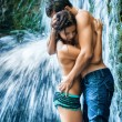Couple hugging and kissing under waterfall - Stock Photo