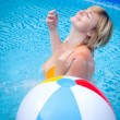 Stock Photo: Happy attractive woman with beach ball in swimming pool