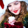 Beautiful woman in a red dress and hat of Santa with a candle — Stock Photo