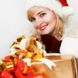 Beautiful woman in a red dress and hat of Santa with a big gift — Stock Photo