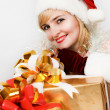 Beautiful woman in a red dress and hat of Santa with a big gift — Stock Photo #13276411