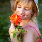kvinnan gör trädgårdsarbetet sniffa på rose — Stockfoto