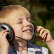Relaxed little boy listening music in park — Stock Photo #13276447