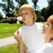 Mother with the son with dandelions in hands — Stock Photo