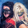 Happy young girls under masks on the party - Stock Photo