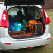Hatchback car loaded with open trunk and luggage - Stock Photo