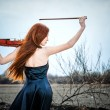 The red-haired girl with a violin outdoor — Stock Photo #13276629