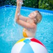 Happy attractive woman with beach ball in swimming pool — Stock Photo