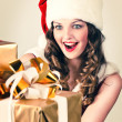 Beautiful woman in a red dress and hat of Santa with a big gift - 